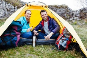 53949165-couple-sitting-in-a-tent-camping-near-the-rocks